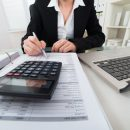 © Andreypopov | Dreamstime.com - Businesswoman Calculating Invoice Photo